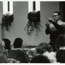 Tony Tyznik holding up twig while teaching a class