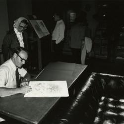 Tony Tyznik signing his artwork for woman at table