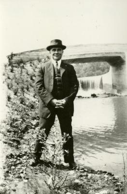 John Van Gemert standing at edge of water in front of bridge and dam