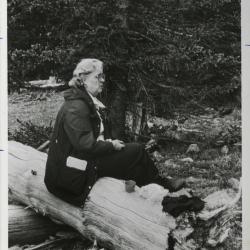 """Elizabeth """"Sody"""" Zimmerman seated on fallen tree trunk"""