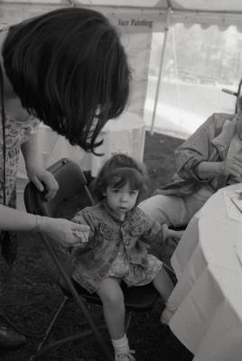 Arbor Day activities at The Morton Arboretum, girl holding woman's hand at Face Painting station