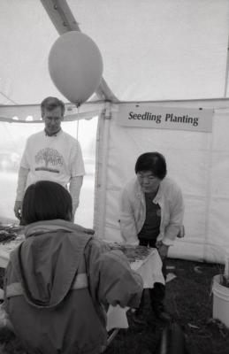 Arbor Day activities at The Morton Arboretum, child at Seedling Planting station talking to Tom Simpson and Heidi Tamanaha