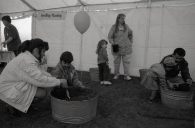 Arbor Day activities at The Morton Arboretum, boy planting plant with woman in barrel of dirt next to Seedling Planting station