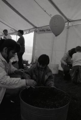 Arbor Day activities at The Morton Arboretum, boy working with woman in barrel of dirt next to Seedling Planting station