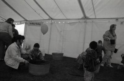 Arbor Day activities at The Morton Arboretum, boy scooping dirt with woman in barrel next to Seedling Planting station