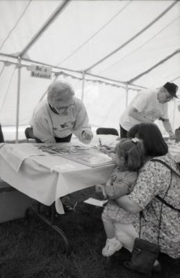 Arbor Day activities at The Morton Arboretum, girl and woman creating Herbarium specimen at Be a Botanist station