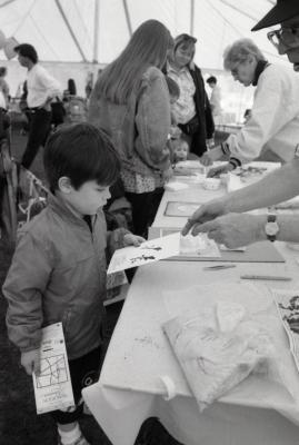 Arbor Day activities at The Morton Arboretum, boy at Be a Botanist station holding Herbarium specimen