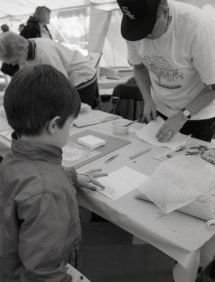 Arbor Day activities at The Morton Arboretum, boy at Be a Botanist station with Herbarium specimens