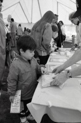 Arbor Day activities at The Morton Arboretum, boy at Be a Botanist station touching bag of material