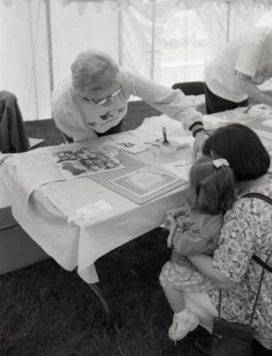 Arbor Day activities at The Morton Arboretum, woman assisting girl and woman create Herbarium specimen at Be a Botanist station