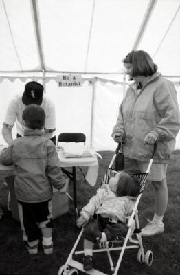 Arbor Day activities at The Morton Arboretum, woman and two children at Be A Botanist station