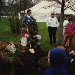 Arbor Day, child and Carolyn Finzer dressed as Morton Oak planting tree, Scott Mehaffey speaking on microphone to crowd