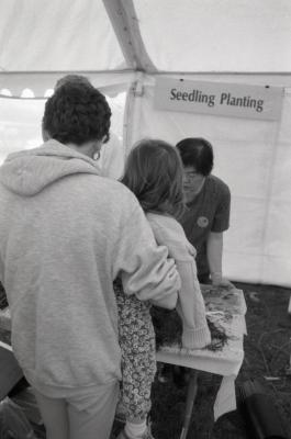 Arbor Day activities at The Morton Arboretum, woman holding girl up over Seedling Planting station