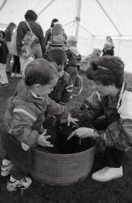 Arbor Day activities at The Morton Arboretum, woman and two boys transferring plant to dirt in barrel next to Seedling Planting station