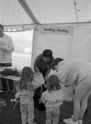 Arbor Day activities at The Morton Arboretum. Tom Simpson (left) and Heidi Tamanaha, volunteer, helping two girls and woman at Seedling Planting station