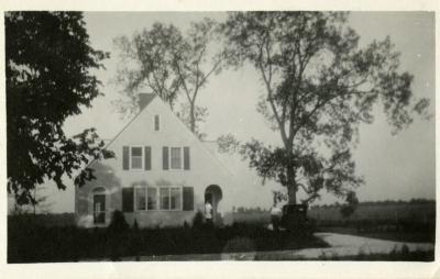 Clarence Godshalk's first Arboretum house, front exterior view, Harriet standing in doorway, Clarence at car