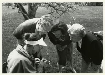 Arbor Day/Week, Ruth Luthringer and two others examining flower with a lens