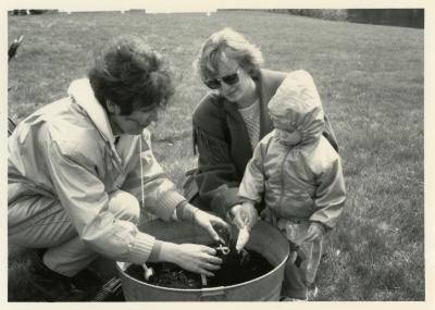 Arbor Day, Susan Klatt and two visitors tree planting in barrel