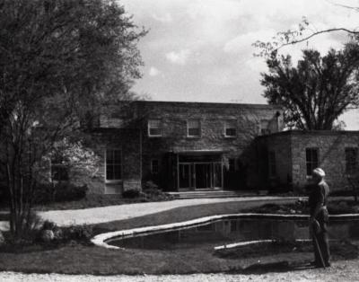 Administration Building with new front entrance, man standing next lily pond