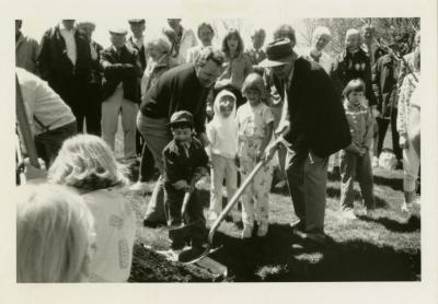 Arbor Day, two men and three children planting tree with surrounding crowd