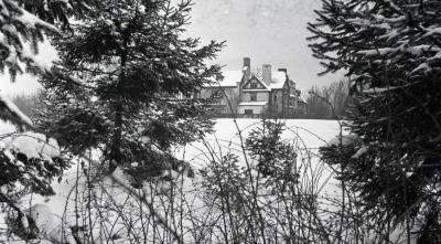 Winter view between evergreens of Morton residence southeast side