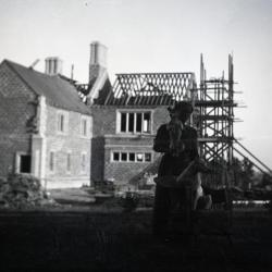 Jane Morton with two dogs in front of Morton residence construction at Thornhill