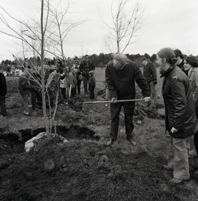 Arbor Day Centennial, Centennial Grove tree planting, group of people watch man shovel dirt over newly planted tree
